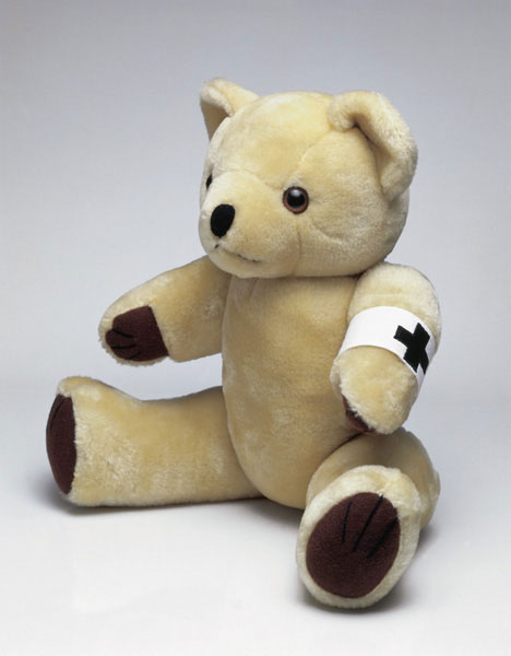 Ursula Noordnung Bear, plush teddy bear with embroidered armband (Malevich cross), approximately 39 x 21 x 16 cm, 2000